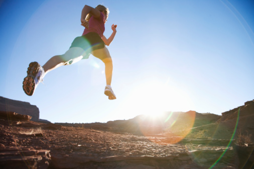 Woman running over rocks, low angle view